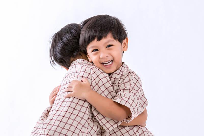 Zwillingsbrüder, die sich gegenseitig umarmen und lächeln