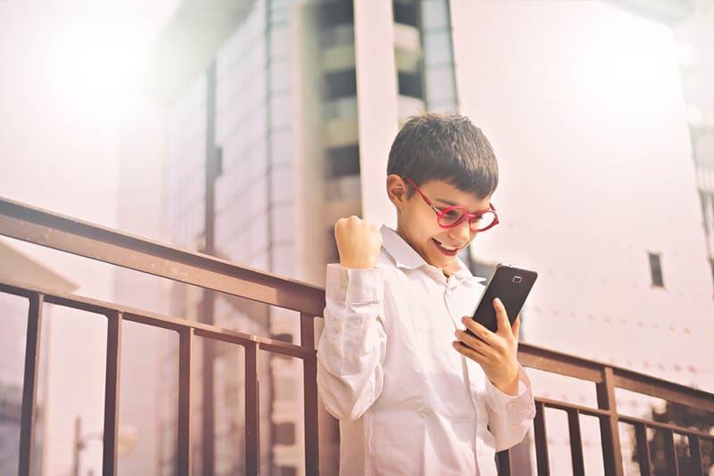 aufgeregtes Kind, das im Freien auf sein Smartphone schaut