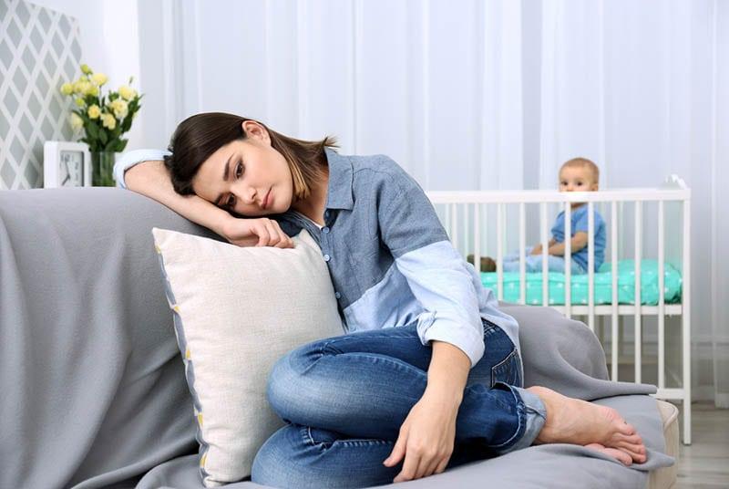 depressive Frau sitzt auf der Couch, während Baby in der Krippe ist