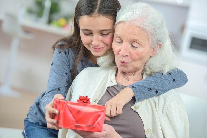 ein Mädchen, das seiner Großmutter ein Geschenk zum Geburtstag macht