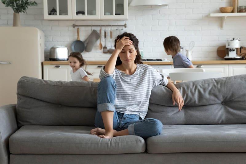 erschöpfte Frau sitzt auf der Couch, während Kinder laufen