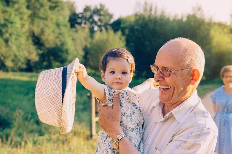 glücklich Großvater hält süße Enkelin in den Armen im Freien