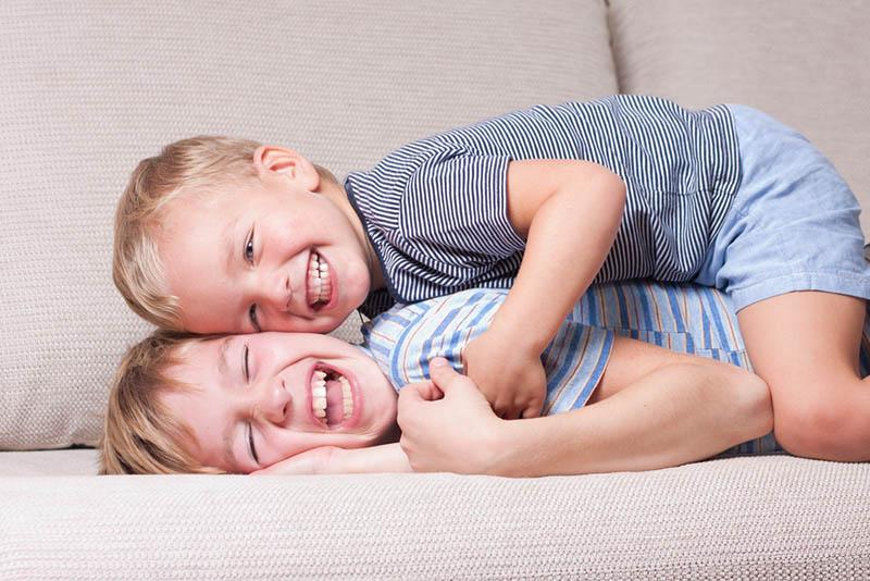 glückliche Brüder kitzeln auf der Couch