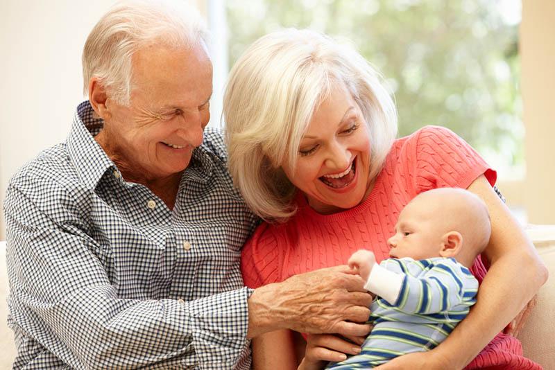 glückliche Großeltern spielen mit Baby