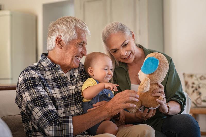 glückliche Großeltern spielen mit Enkel auf der Couch