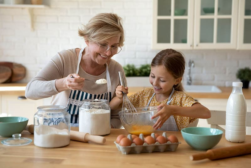 glückliche Großmutter Kochen zusammen mit ihrer Enkelin in der Küche