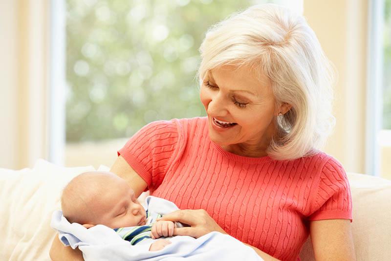glückliche Großmutter hält ihren Enkel in den Armen