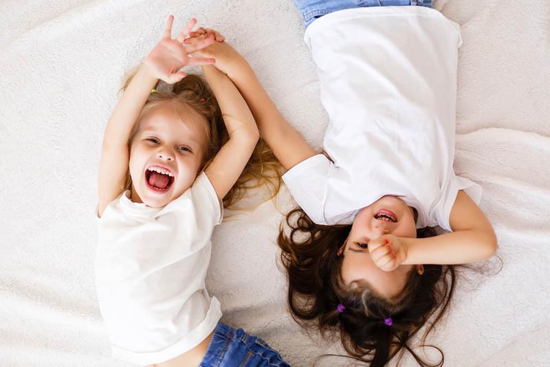 glückliche kleine Mädchen auf dem Bett liegend