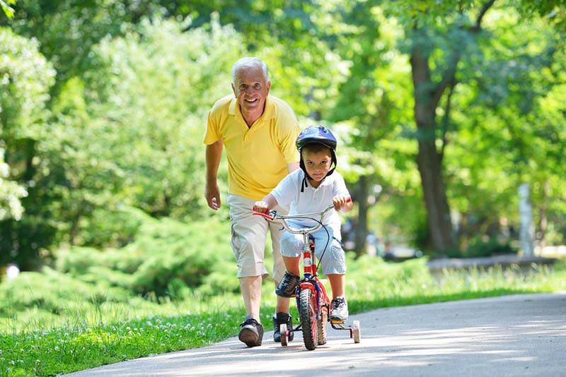 glücklicher Großvater, der seinem Enkel das Fahrradfahren beibringt