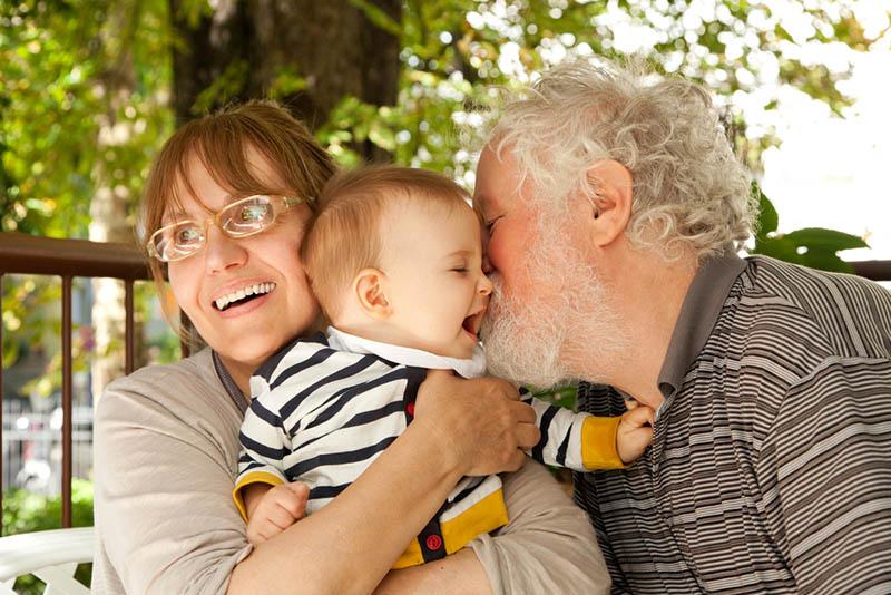 glücklicher Großvater, der seinen Enkel küsst