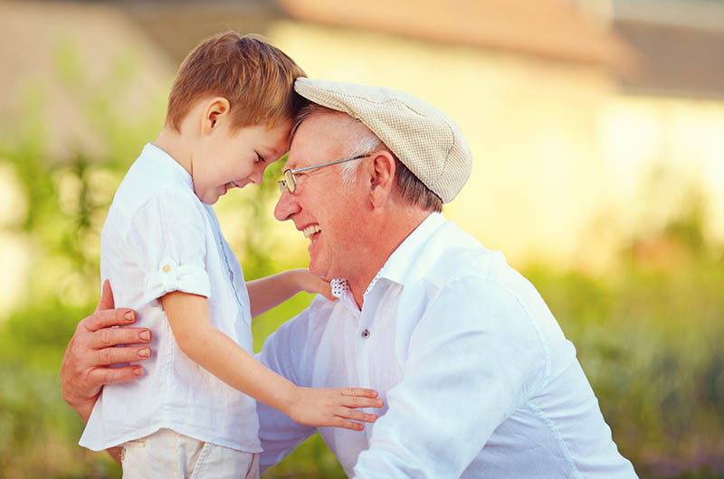 glücklicher Großvater und Enkel verneigen sich