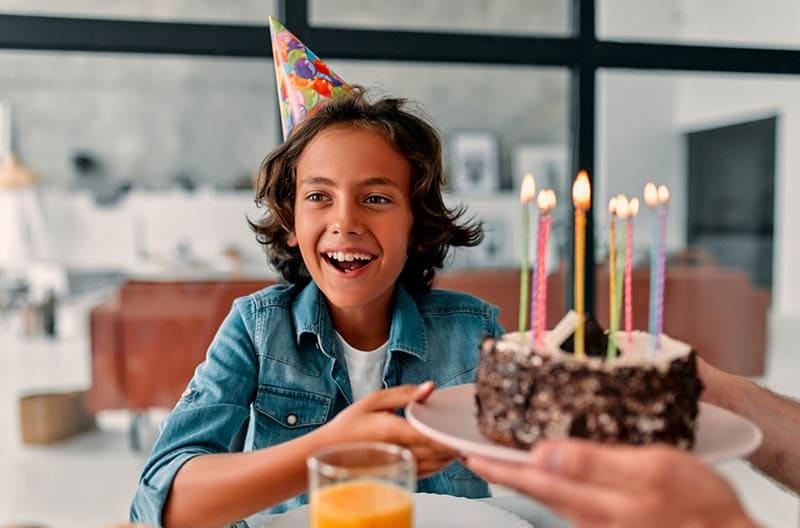 glücklicher Junge feiert Geburtstag mit Kuchen und Kerzen