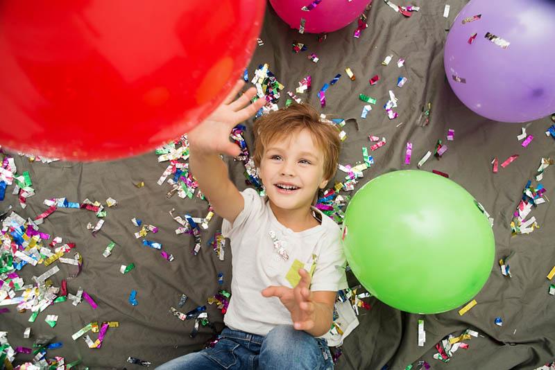 glücklicher Junge spielt mit Luftballons