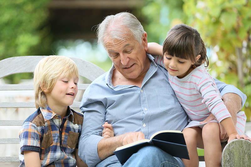 glücklicher Opa, der seinen Enkeltöchtern auf der Bank ein Buch vorliest