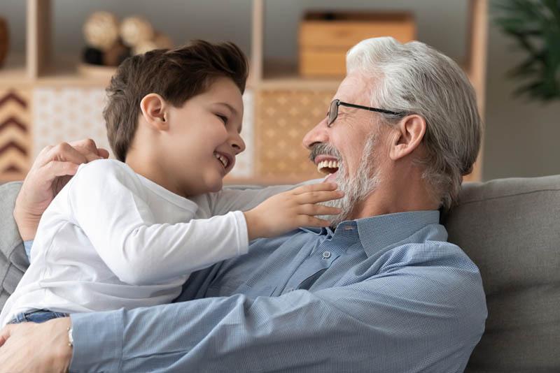 glücklicher Opa lachend mit Enkel auf der Couch