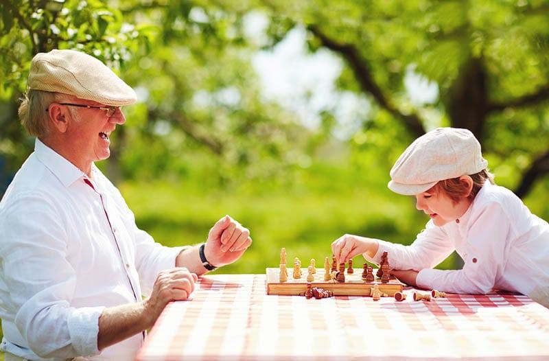 glücklicher Opa und Enkel spielen Schach im Frühlingsgarten
