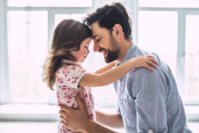 glücklicher junger Vater umarmt mit seiner kleinen Tochter