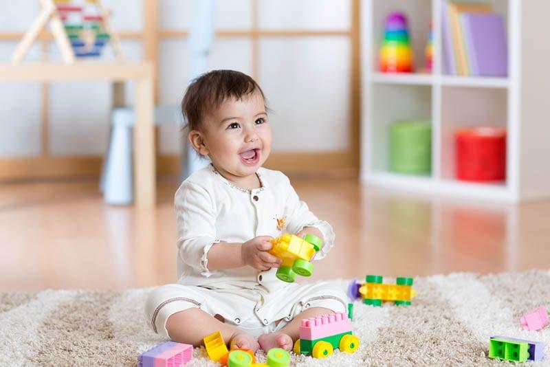 glückliches Baby spielt mit Lego-Würfeln auf dem Boden