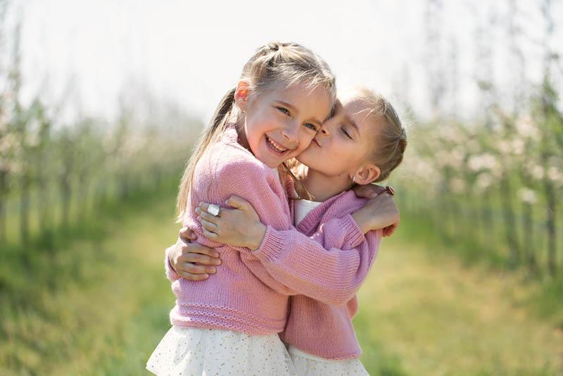 glückliches kleines Mädchen küsst ihre Schwester im Freien