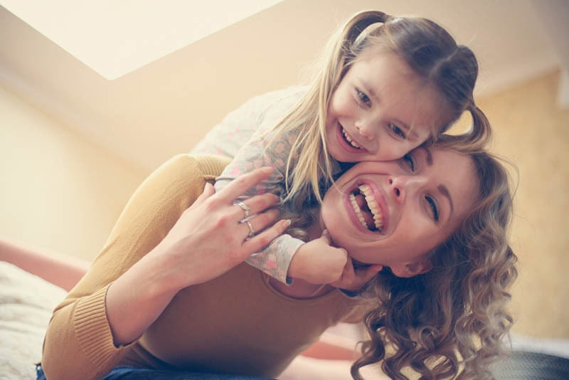 glückliches kleines Mädchen spielt mit ihrer Mutter zu Hause