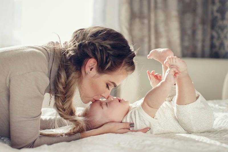 junge Mutter küssen niedlichen Baby in Stirn auf dem Bett