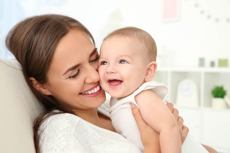 junge glückliche Mutter hält lächelnd niedlichen Baby auf der Couch