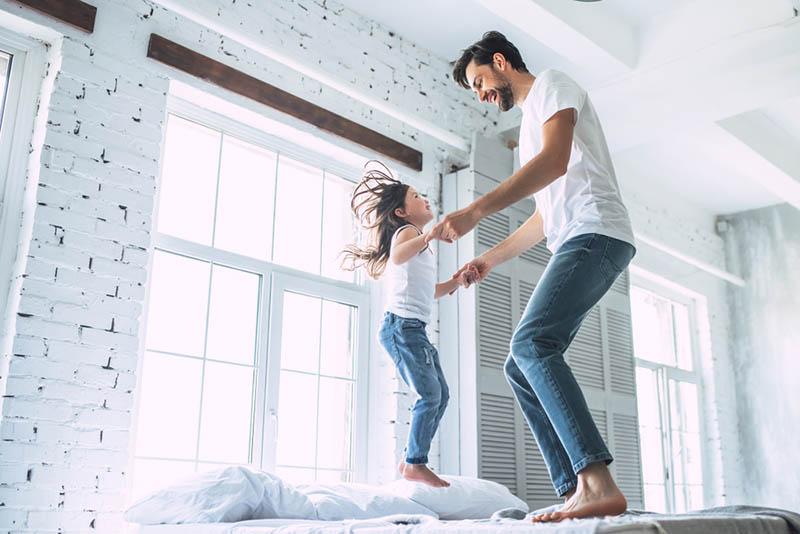 junger Vater springt mit Tochter auf das Bett