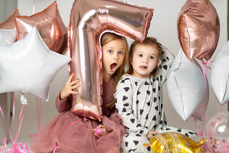 kleine Mädchen sitzen mit Geburtstagsballons auf dem Boden