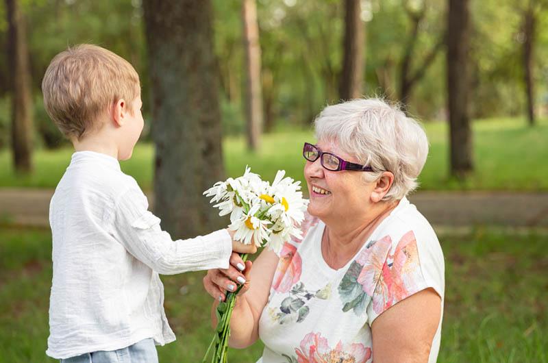 kleiner Junge gibt seiner Großmutter Blumen