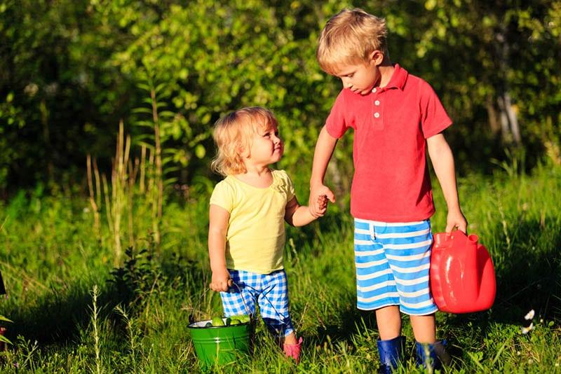 kleiner Junge hält seinen kleinen Bruder für Hände im Garten