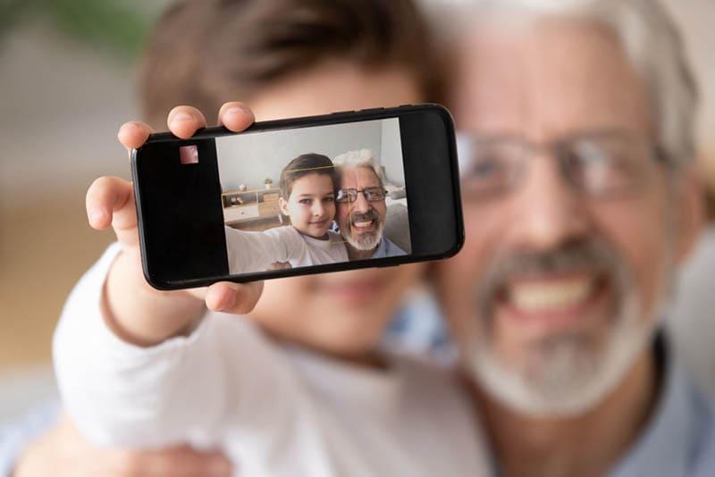 kleiner Junge nimmt ein Selfie mit seinem Opa