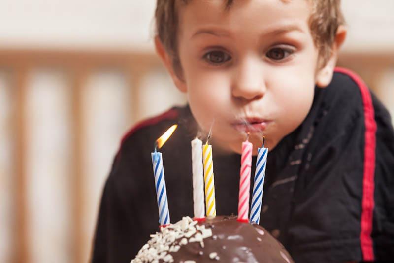 kleiner Junge pustet Geburtstagskerzen auf Kuchen