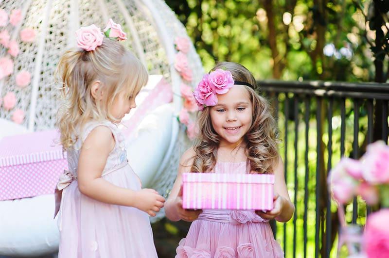 kleines Kind geben einen Geburtstag Geschenk-Box zu ihrer Schwester