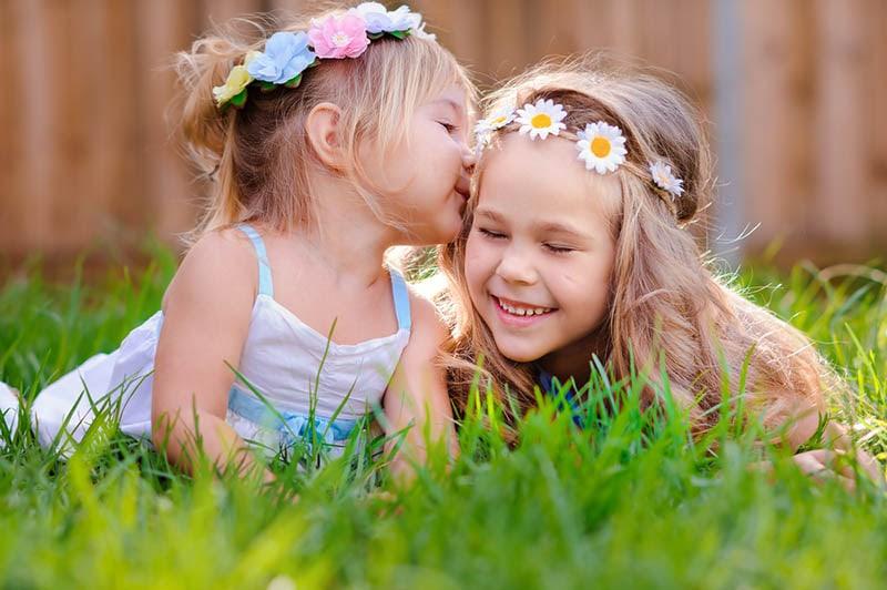 kleines Mädchen küsst ihre ältere Schwester im Gras