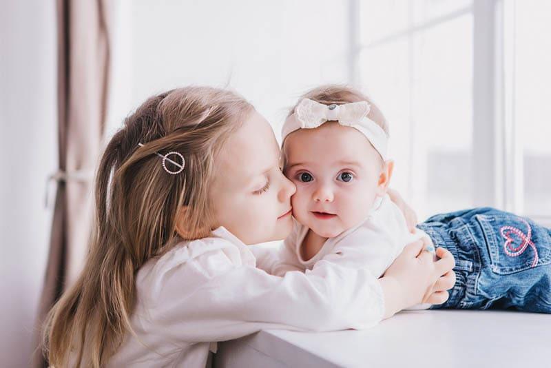 kleines Mädchen küsst ihre kleine Schwester in der Nähe von Fenster