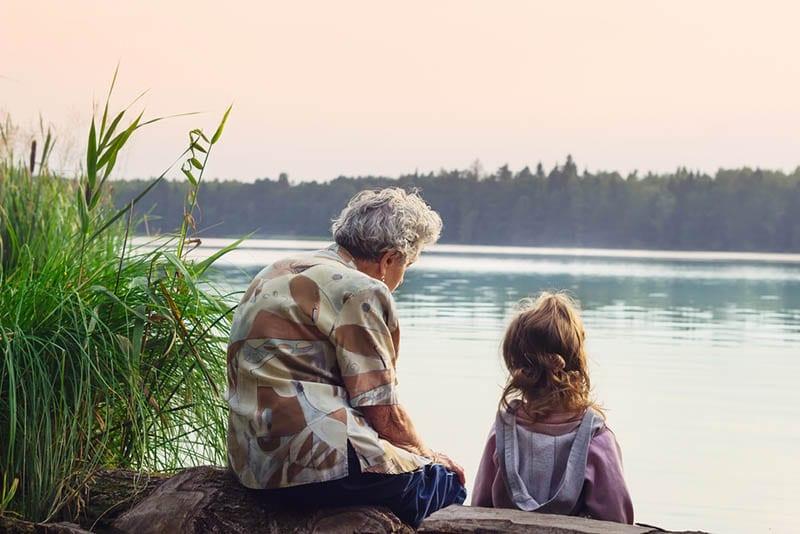 kleines Mädchen sitzt mit Großmutter am Fluss