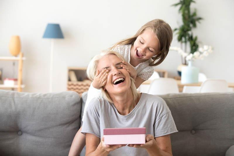 kleines Mädchen überrascht ihre Großmutter mit dem Geschenk