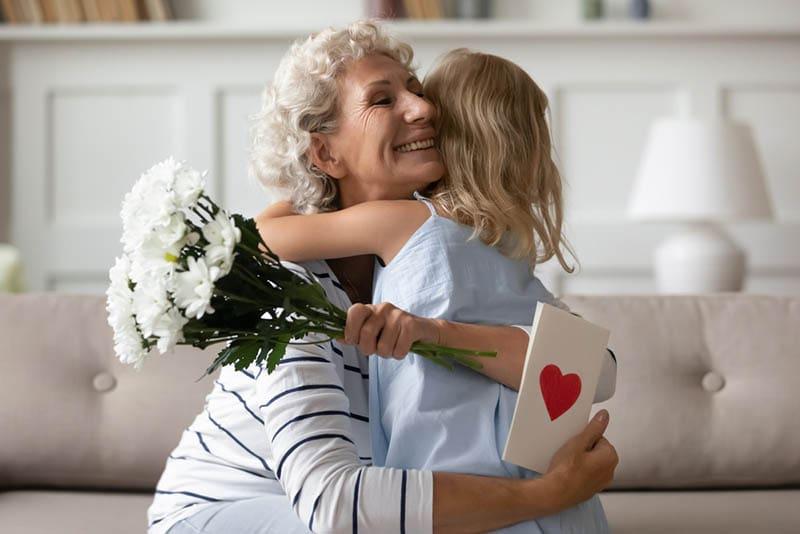 kleines Mädchen umarmt mit ihrer glücklichen Großmutter an ihrem Geburtstag