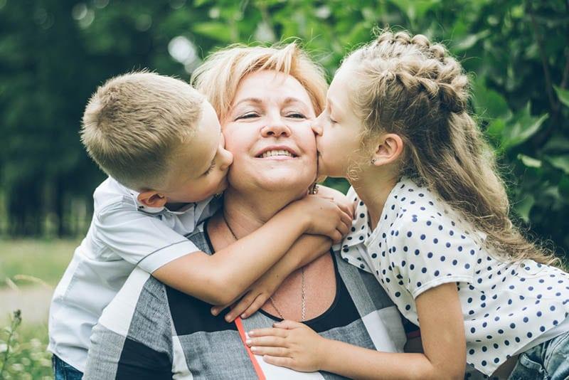 kleines Mädchen und Junge küssen ihre Oma