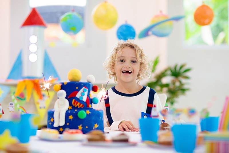 lächelnder Junge feiert Geburtstag mit Kuchen