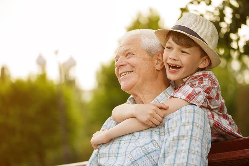 lächelnder kleiner Junge mit Hut, der seinen Opa umarmt
