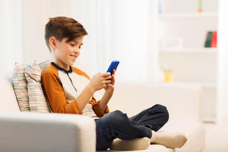 lächelnder kleiner Junge tippt auf Smartphone