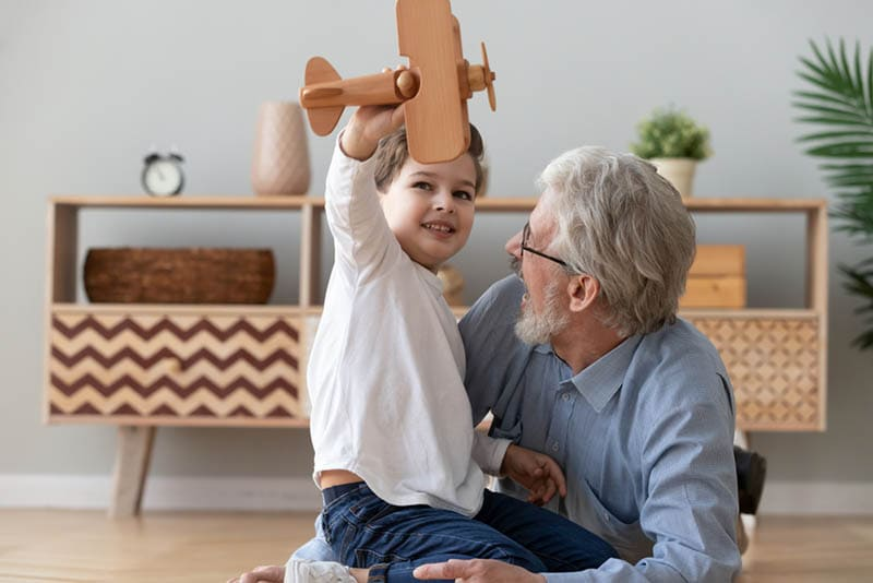 lustiges kleines Enkelkind hat Spaß mit Opa
