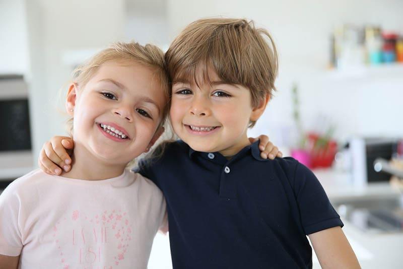niedlich Bruder und Schwester posieren in Umarmung