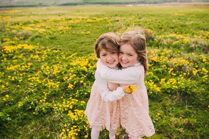 niedlich Schwestern umarmen in der Wiese