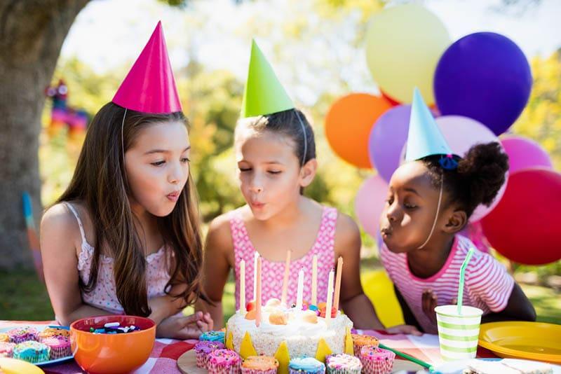 niedlichen Mädchen Blasen auf Kerze während einer Geburtstagsfeier auf einem Park