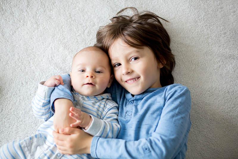 niedlichen kleinen Jungen umarmt sein Baby Bruder auf dem Bett
