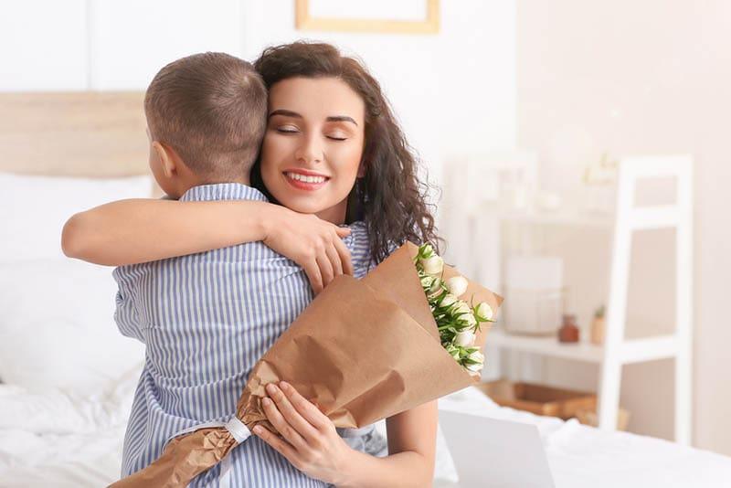 niedlichen kleinen Jungen umarmt seine Mutter an ihrem Geburtstag