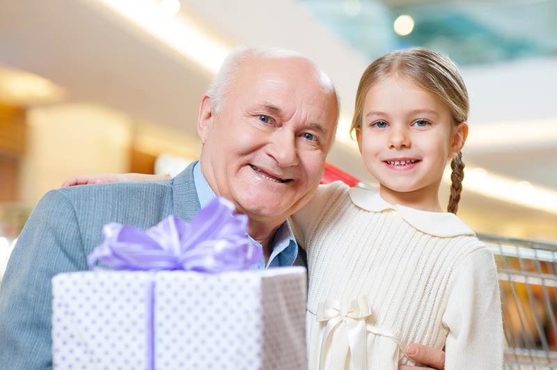 niedlichen kleinen Kind posiert mit ihrem Opa und Geschenk