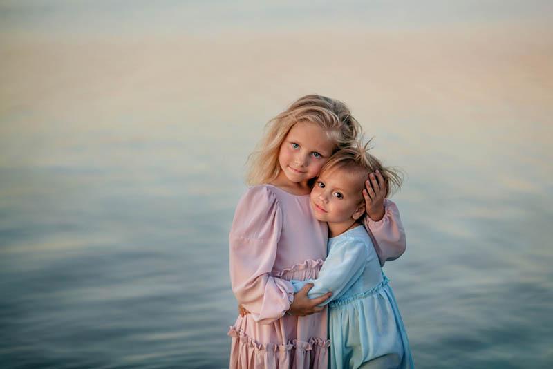 süße Schwestern umarmen durch das Meer am Strand